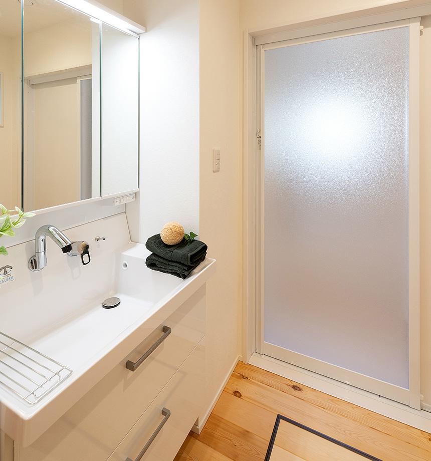 洗面所は清潔感のある白を基調に。床はここも無垢材でやわらかさを出しました。