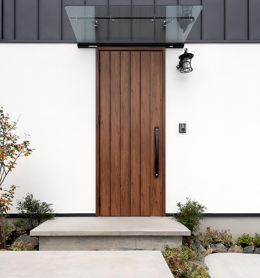 玄関アプローチ。コンクリートの無機質な感じがかっこよさを引き立てます。また、重厚感のある玄関ドア(LIXIL フォーラード)とクリアな庇、少しレトロなアイアンのポーチライトの組み合わせが目を惹きます。