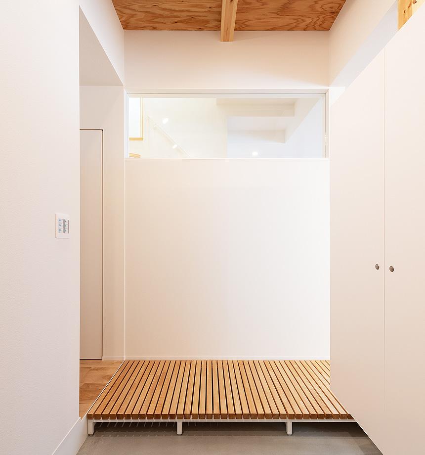 玄関の天井はこだわりのひとつ。土間と梁をみせた木の天井が趣きあります。造作のシューズクローゼットは収納力抜群です。正面のすのこは、リビングとトイレをつなぎます。