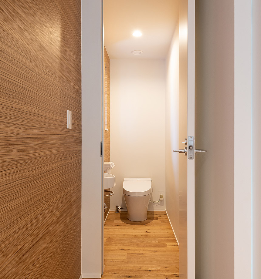 トイレのクロスは室内と同じ柄で一面を貼りわけ、床も室内から続くことで一体感のある空間にしています。
